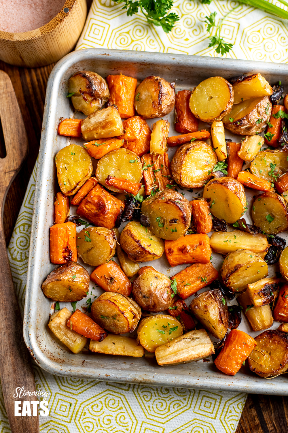 Rosemary Roasted Potatoes, Parsnips, Carrots and Onion on baking tray on wooden board with green pattern tea towel