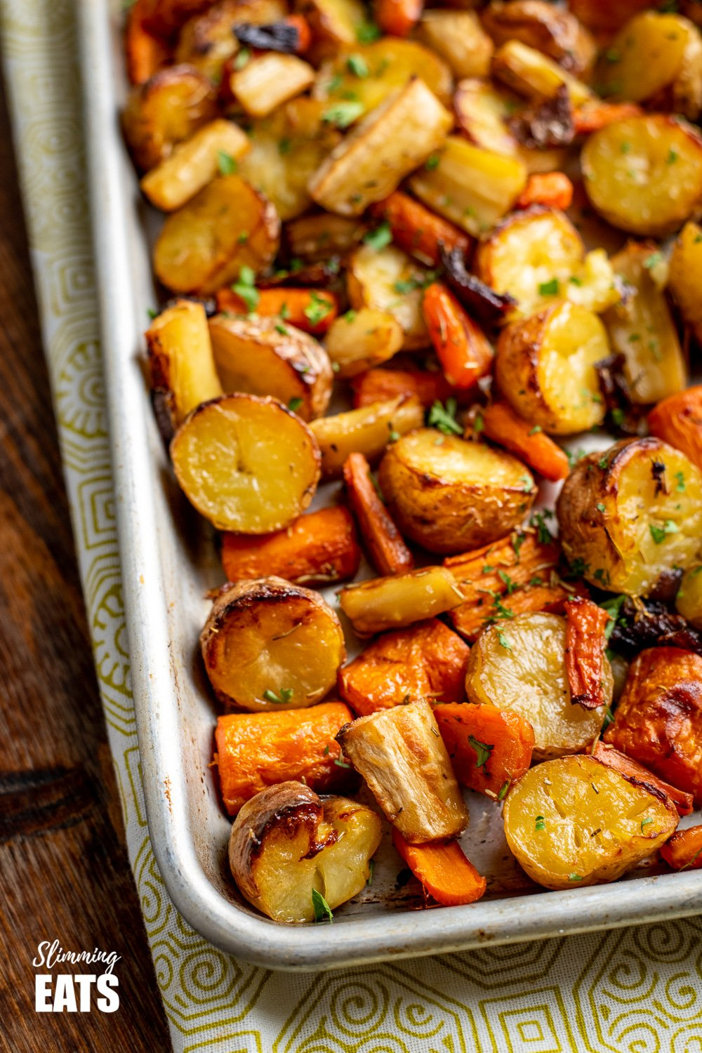 close up of Rosemary Roasted Potatoes, Parsnips, Carrots and Onion on baking tray sprinkled with fresh parsley