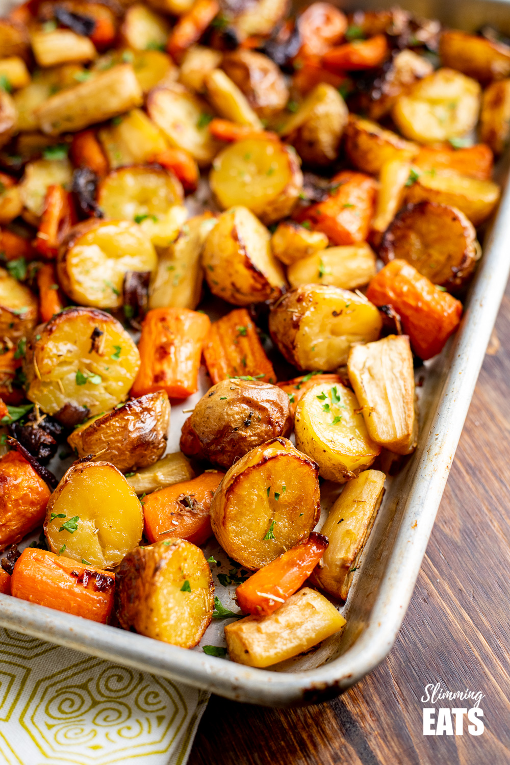 close up of Rosemary Roasted Potatoes, Parsnips, Carrots and Onion on baking tray