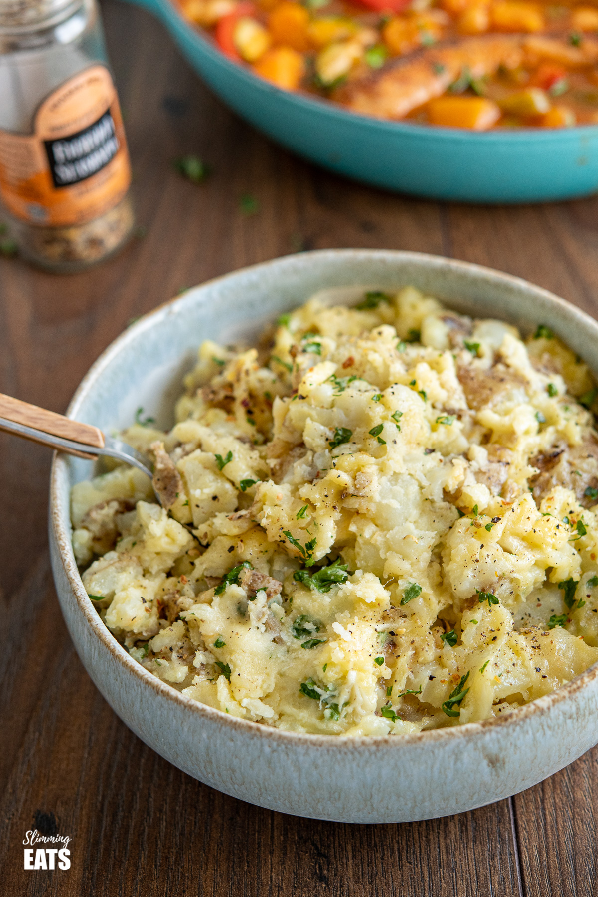 rustic parmesan garlic mashed potatoes in bowl with spoon, sausage casserole in background