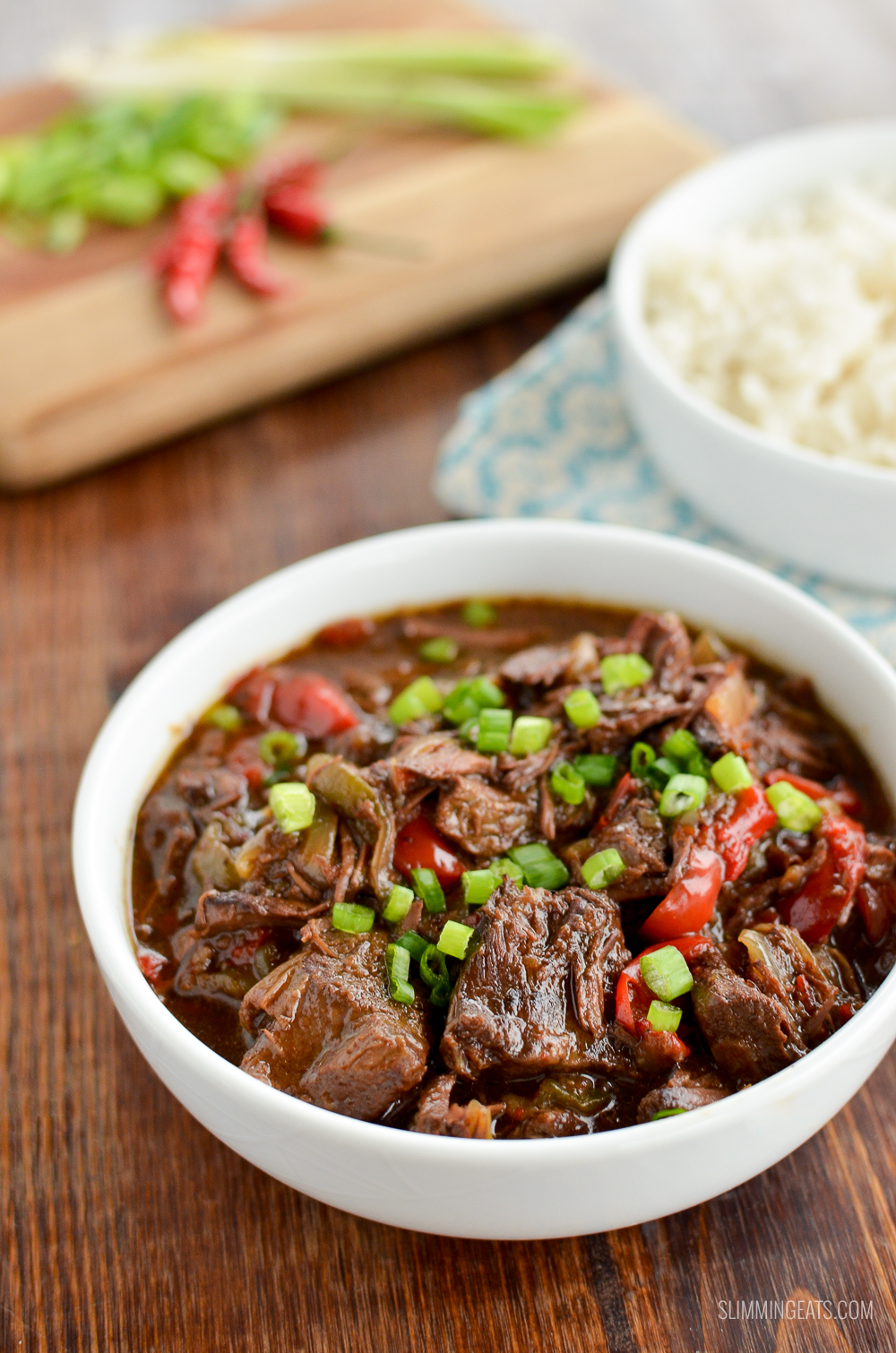 slow cooker spicy Asian Beef in white bowl with chopping board and bowl of white rice in background