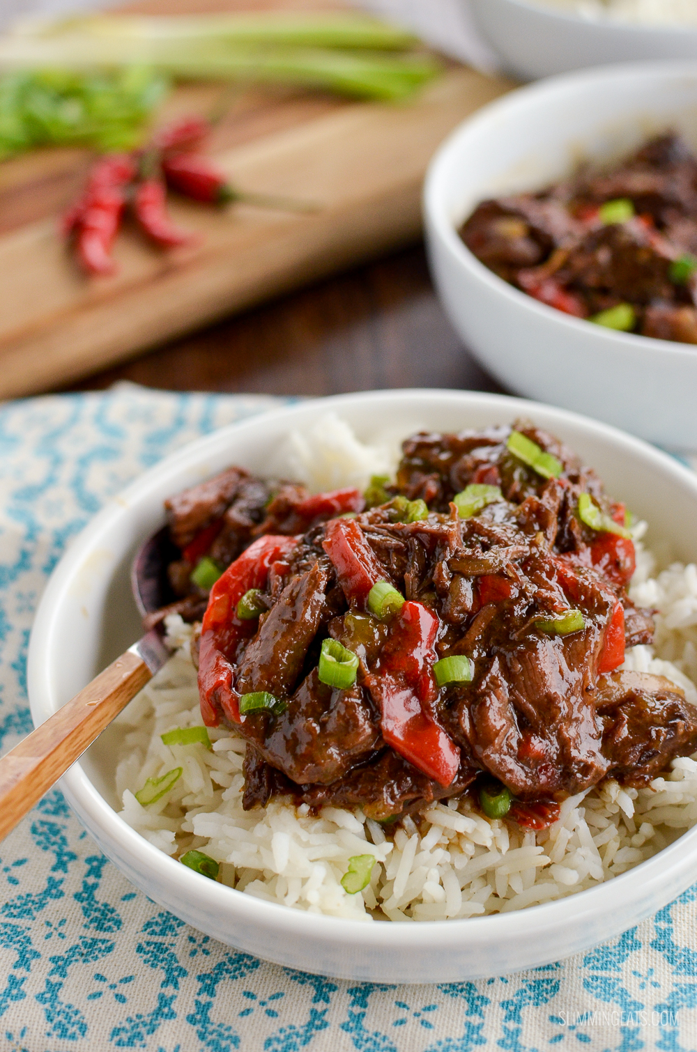 slow cooked spicy asian beef in white bowl with rice and chopping board in background with red chillis