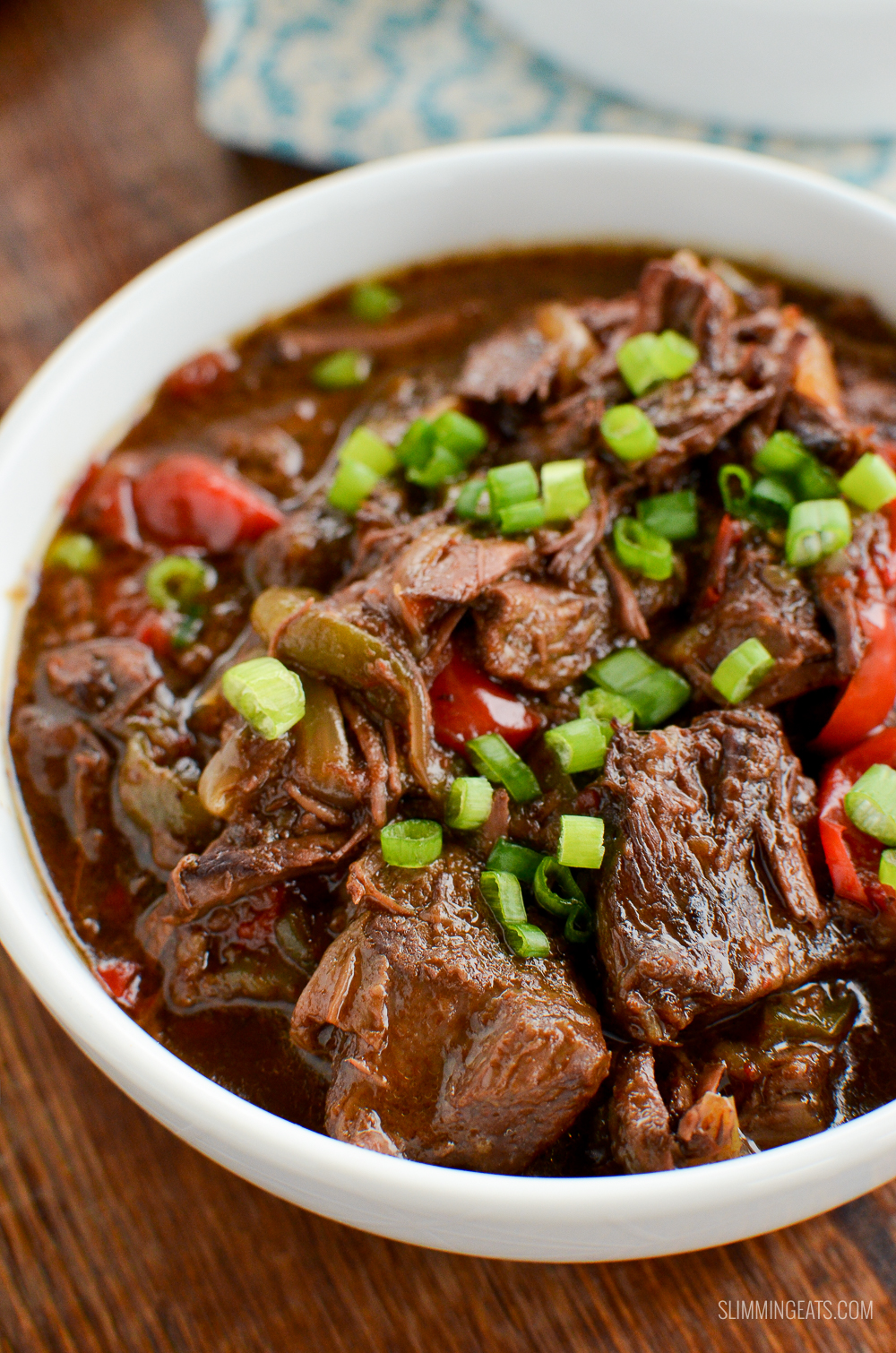 slow cooker spicy Asian Beef in white bowl on wooden board