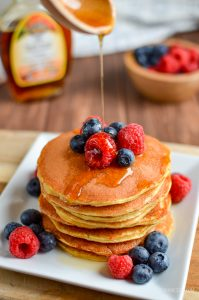 maple syrup being drizzled over american style pancakes and berries