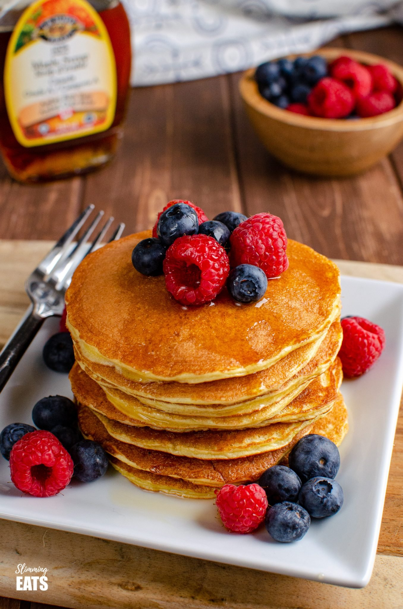 American Style Pancakes on white plate with fruit, maple syrup bottle in background