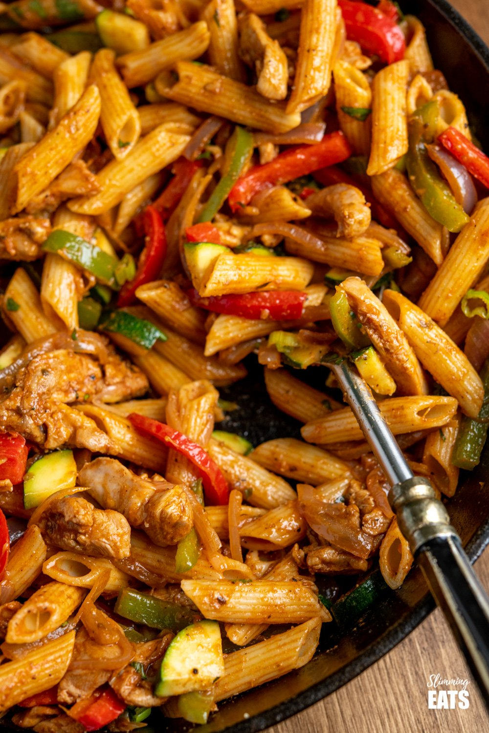 close up of close up of Fajita Chicken Pasta in a lodge cast iron skillet and spoon