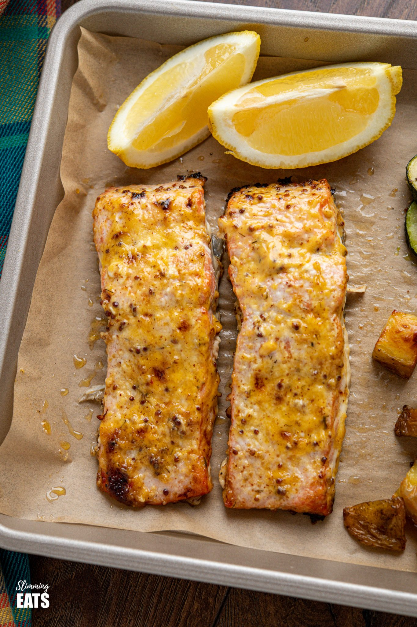 close up of Oven Baked Mustard Salmon Fillets on parchment lined tray with potatoes, zucchini and lemon wedge