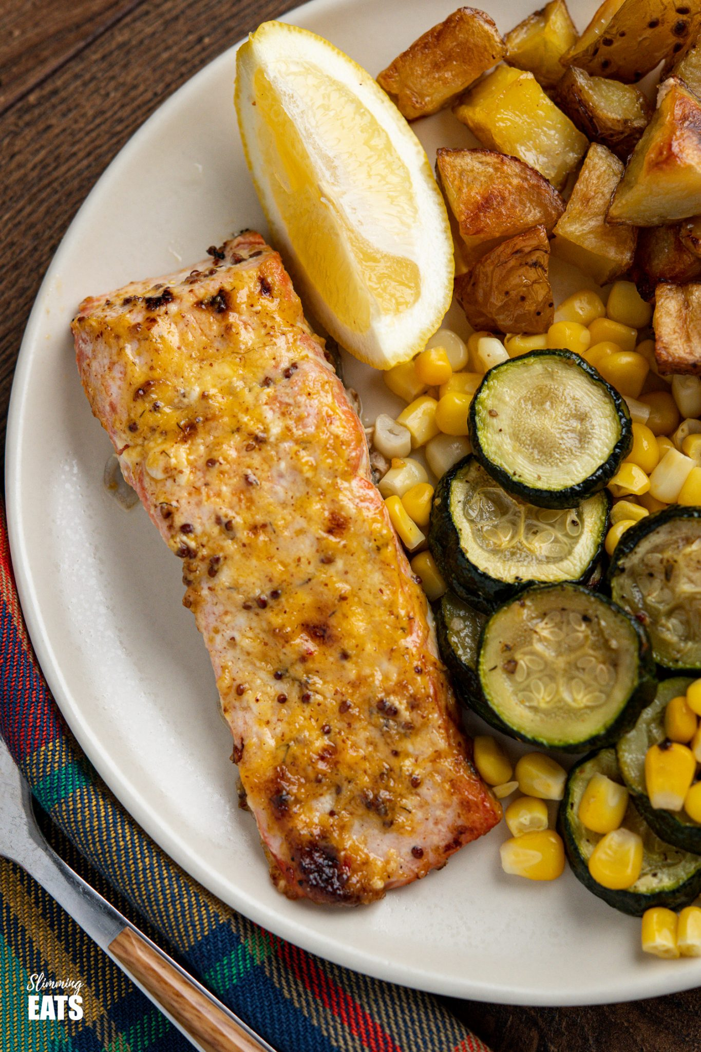 Oven Baked Mustard Salmon Fillets on white plate with roast potato cubes, zucchini and lemon wedge