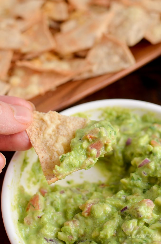 pita chip scooping up pea guacamole from white dish
