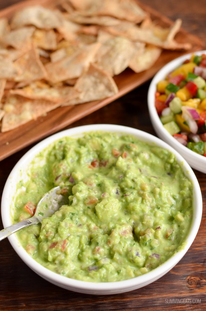 pea guacamole in white dish with spoon and pita chips and mango salsa in background