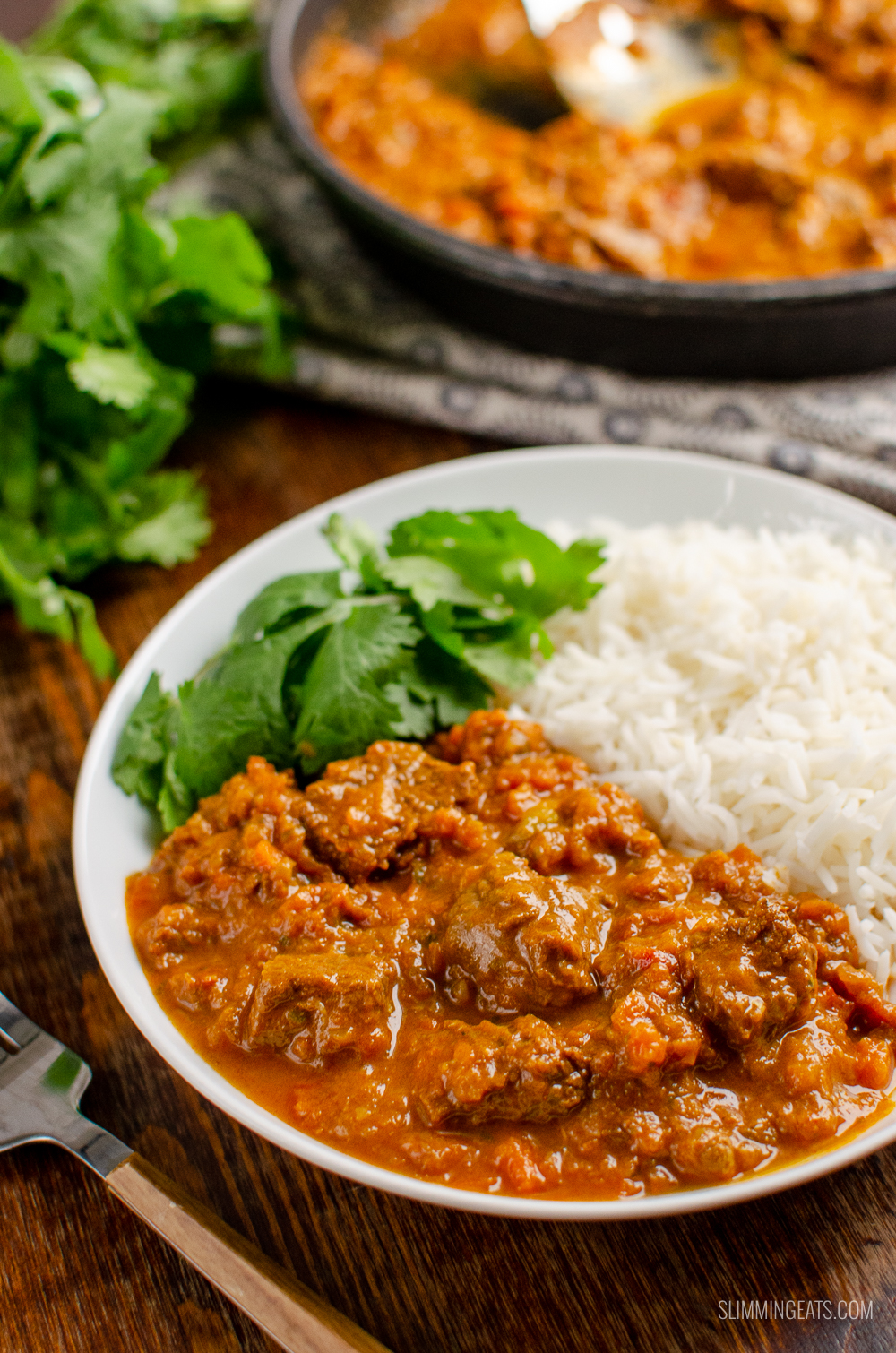 bombay beef curry in white bowl with rice and coriander, pan visible in background