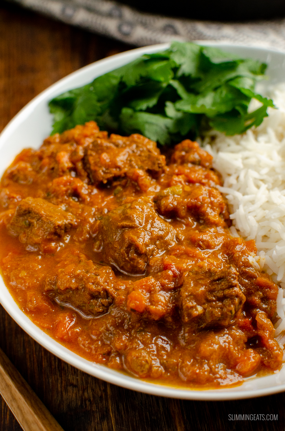 close up of Bombay beef curry in white bowl with rice and coriander.