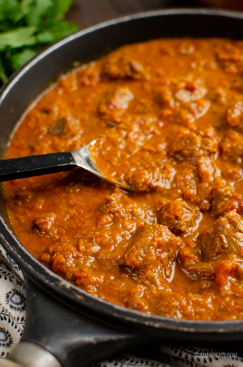 bombay beef curry in a pan with spoon