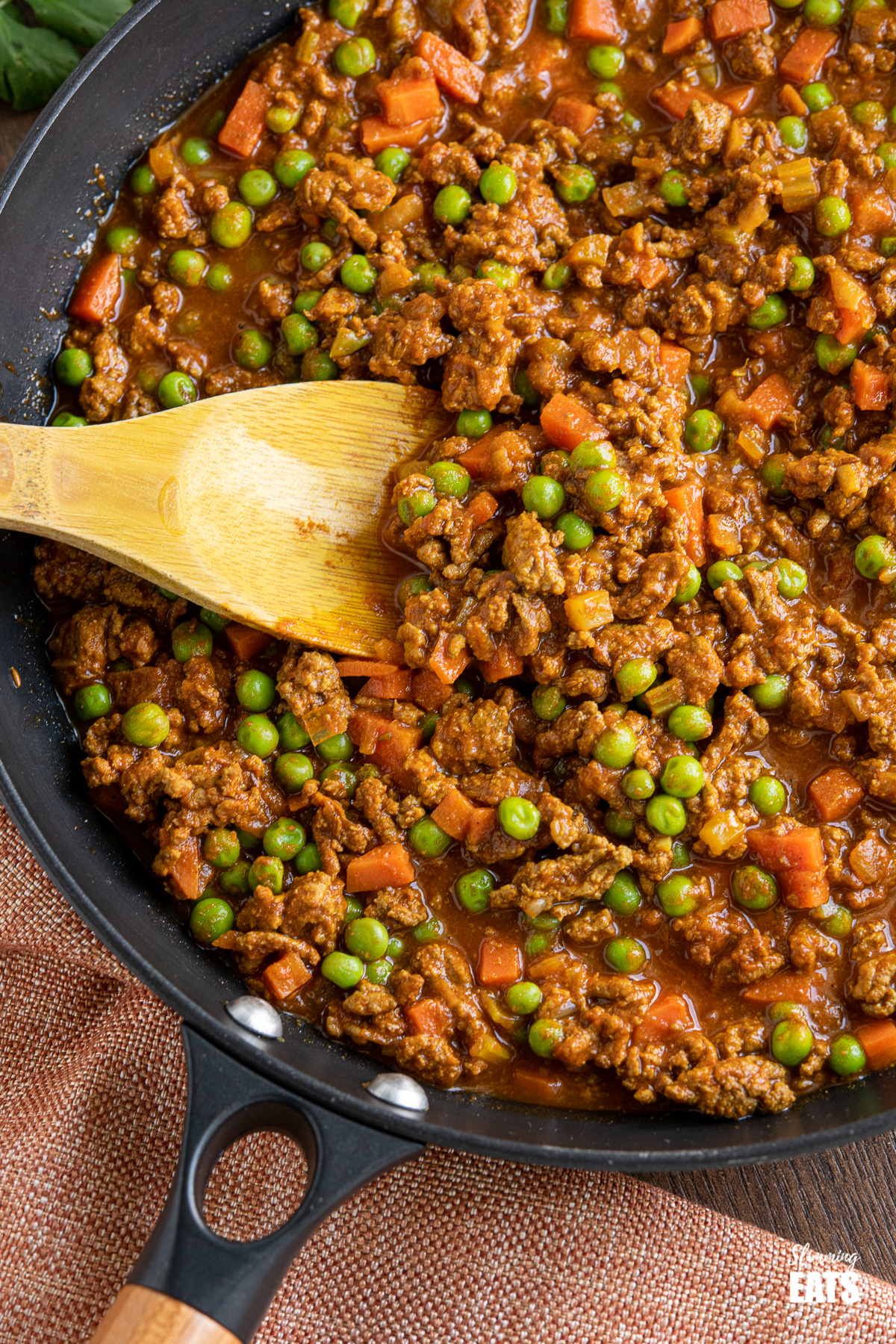 close up of Easy Keema Curry in black pan with wooden spoon