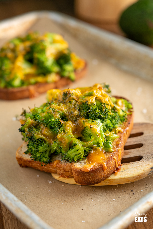 cheesy broccoli avocado toasts on parchment lined baking tray