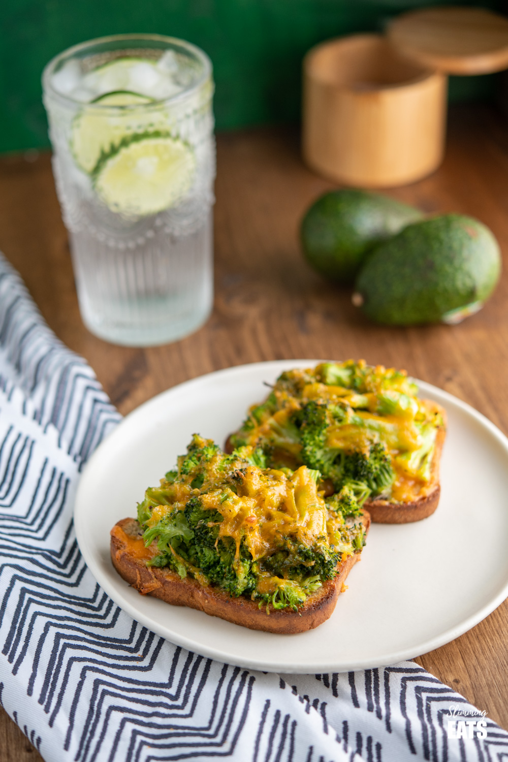 cheesy broccoli avocado toasts on white plate with a glass of lime water and avocados in background