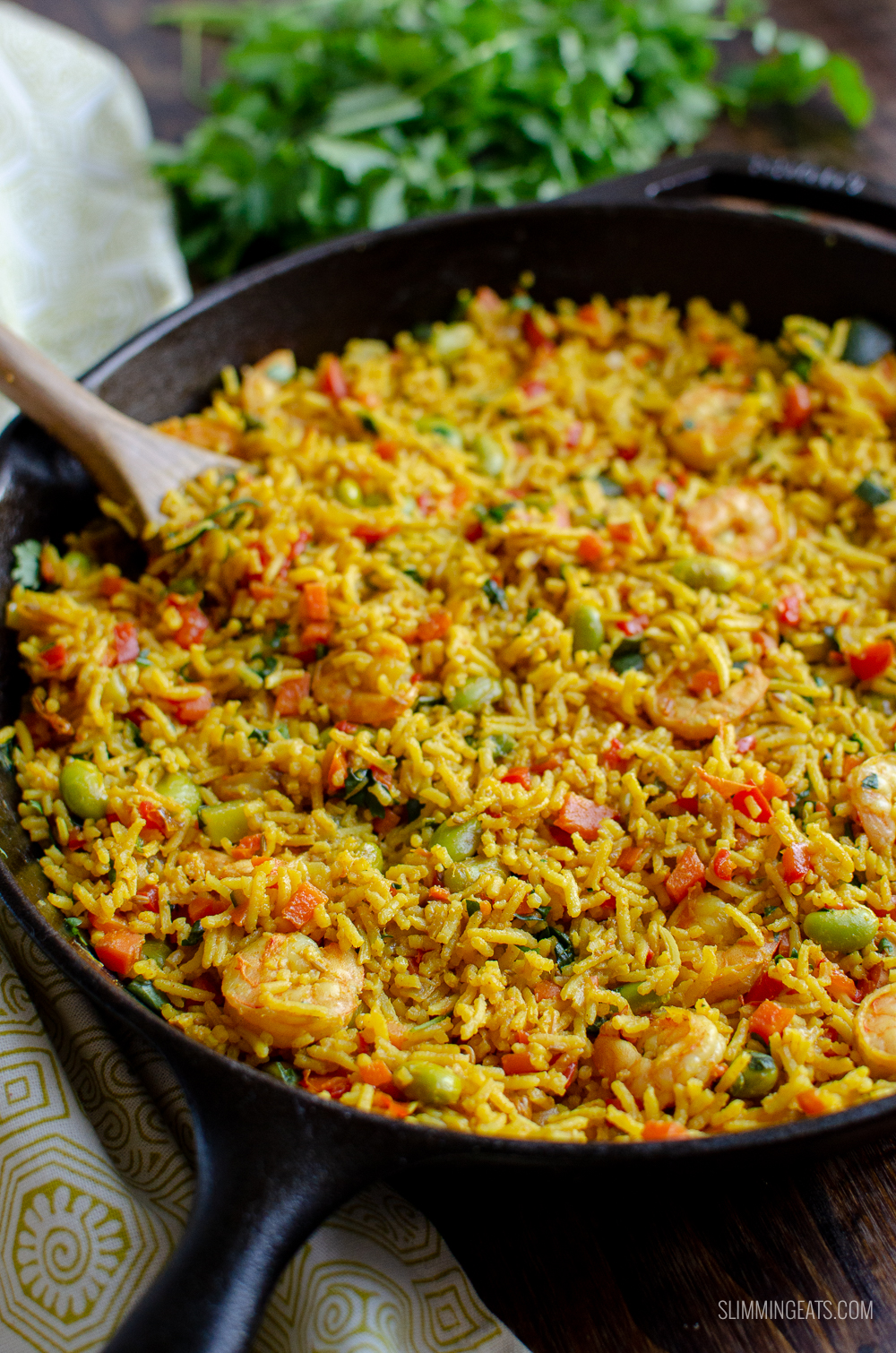 prawn and vegetable pilaf in a cast iron skillet with wooden spoon