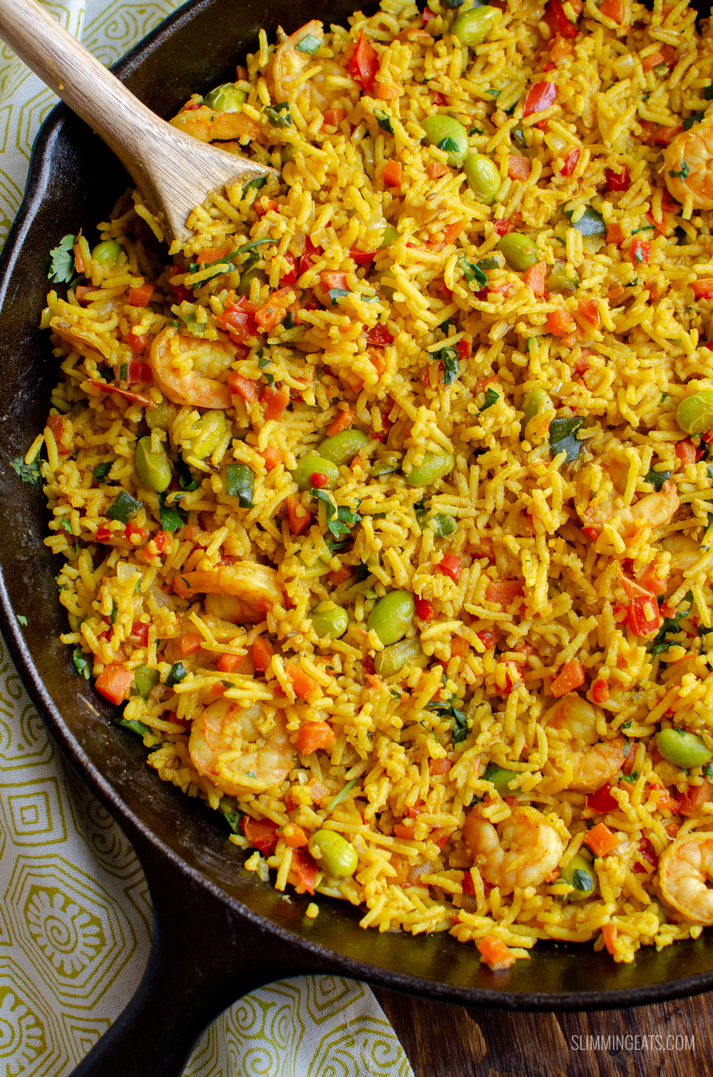 prawn and vegetable pilaf in cast iron skillet with wooden spoon