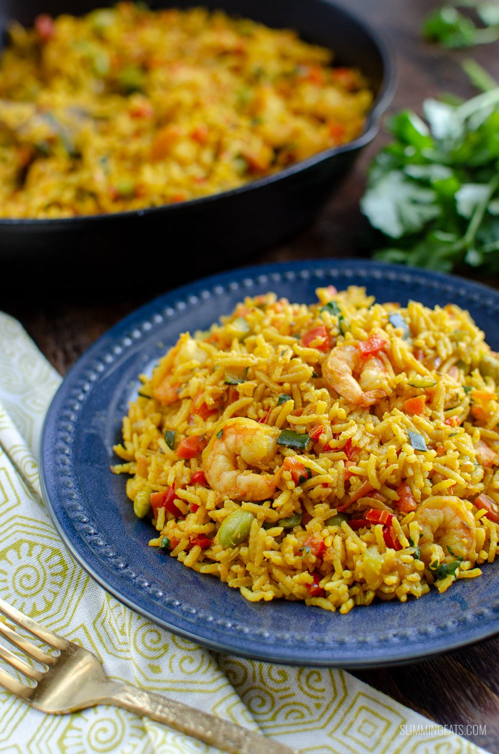 prawn and vegetable rice pilaf on blue plate with skillet in background