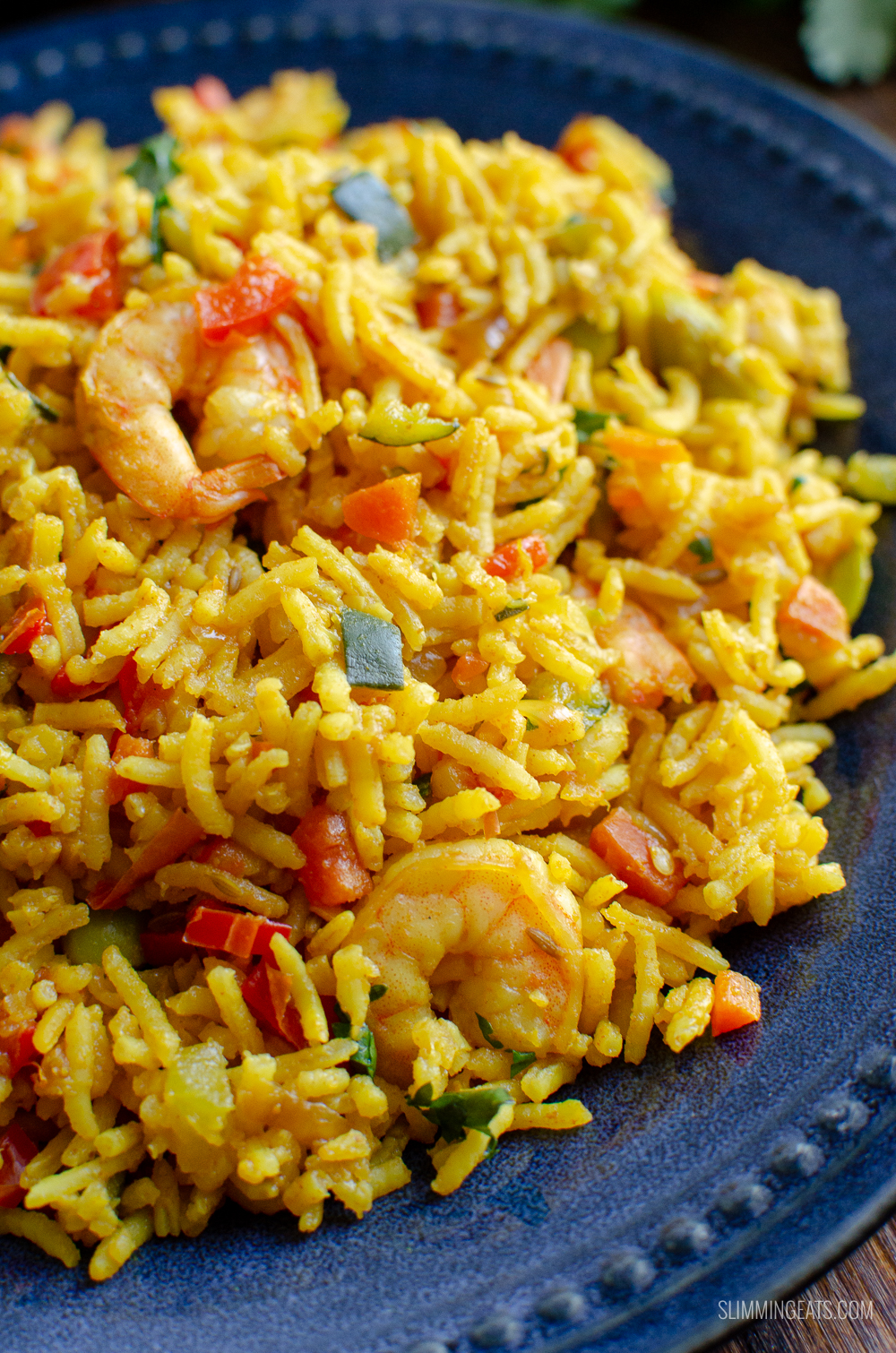 close up of prawn and vegetable pilaf on blue plate
