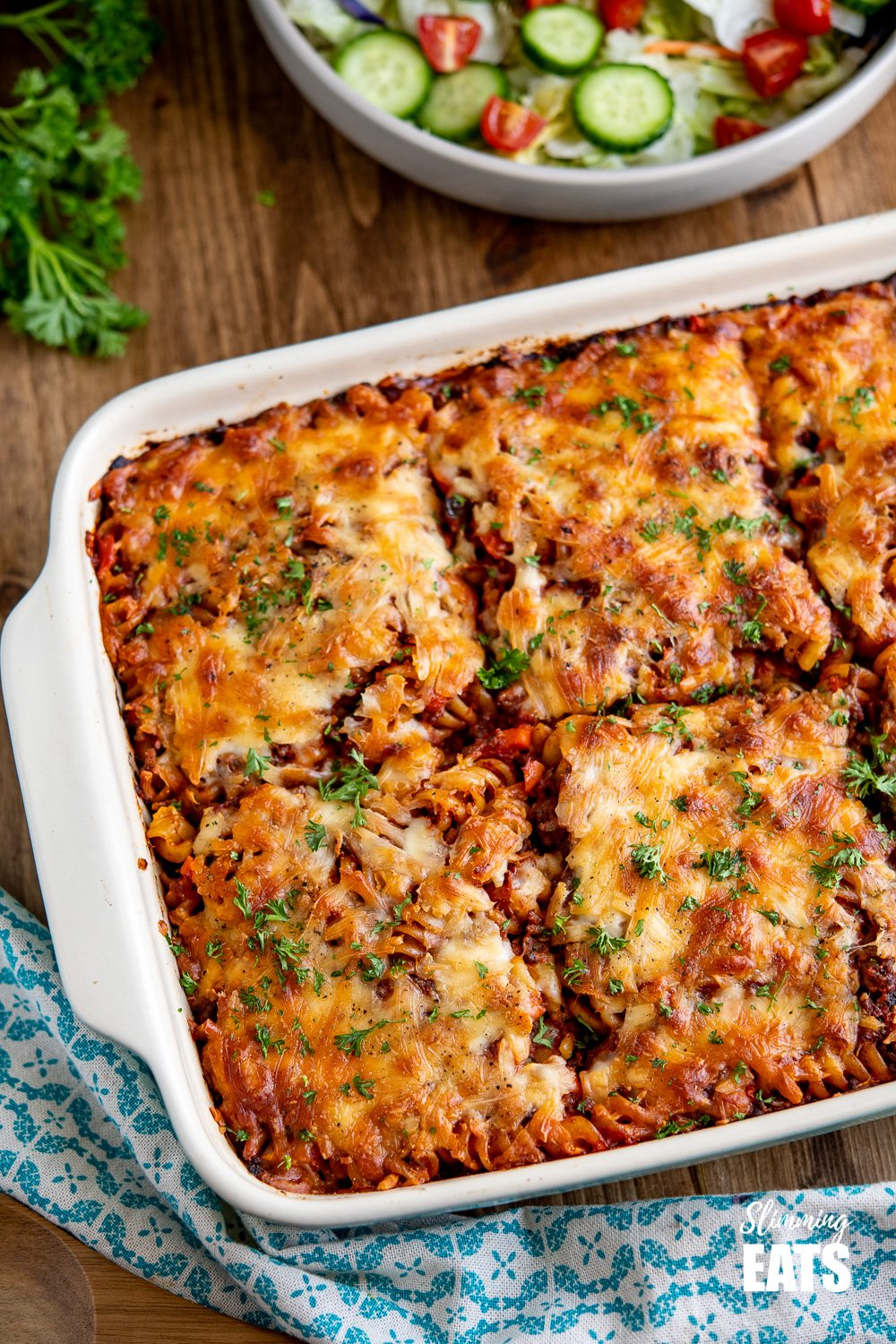 Syn Free Bolognese Pasta Bake in oven dish on wooden board with salad in a bowl