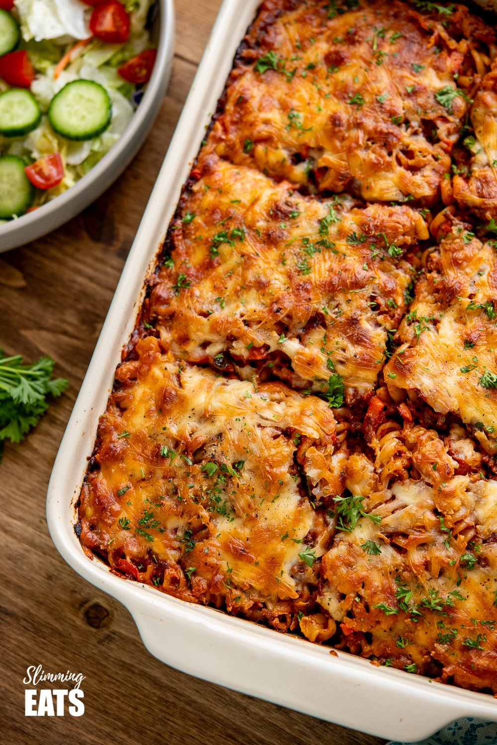 Syn Free Bolognese Pasta Bake in oven proof dish on wooden board with bowl of salad