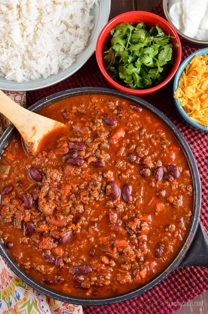 Chilli Con Carne in pan with wooden spoon and bowls with rice, cilantro, cheddar and soured cream.