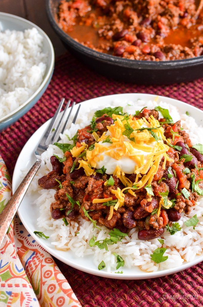 serving of Chilli Con Carne in bowl over rice with toppings