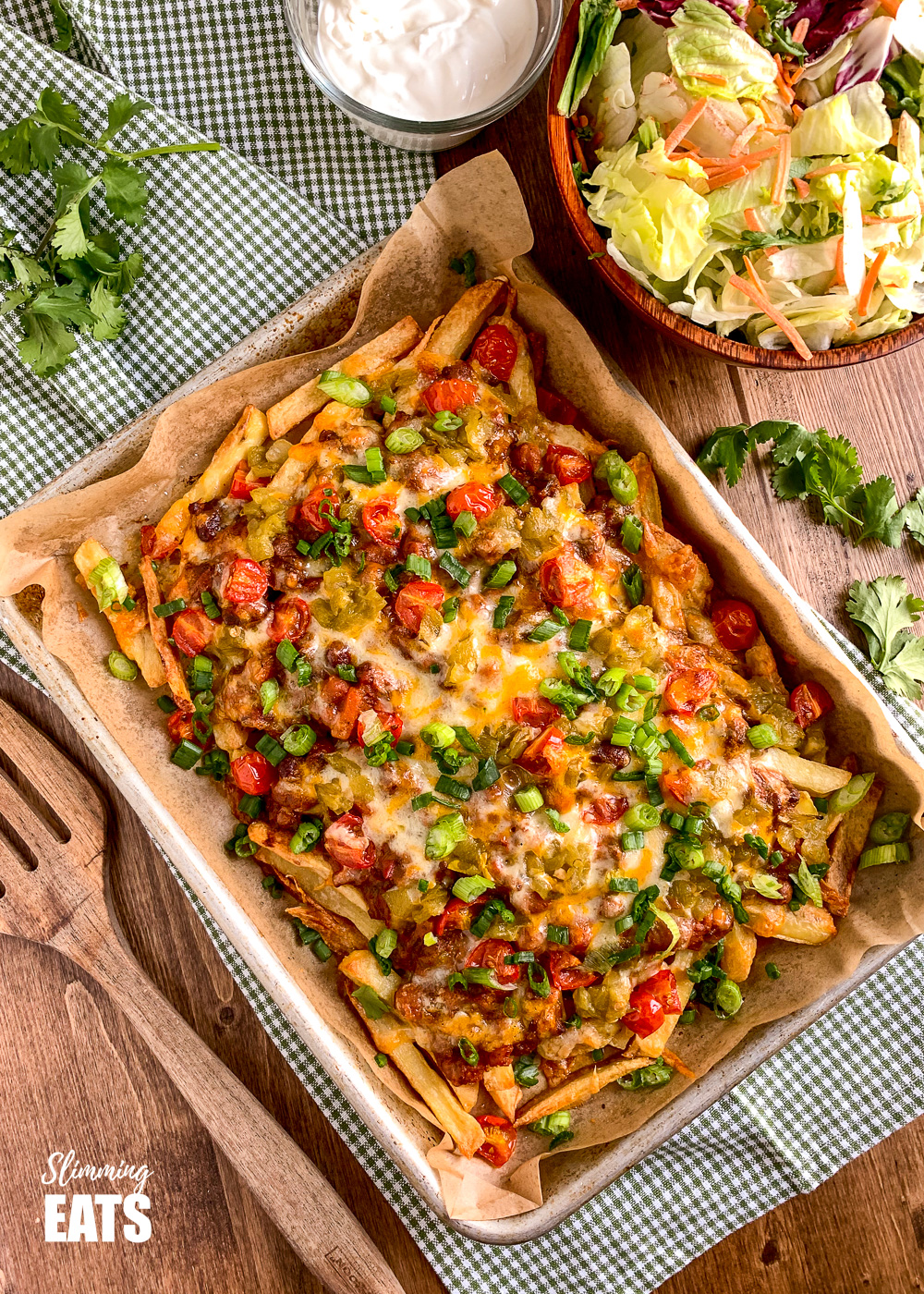 Layered Chilli Cheese Fries on baking tray with salad and soured cream on wooden board with scatter cilatntro