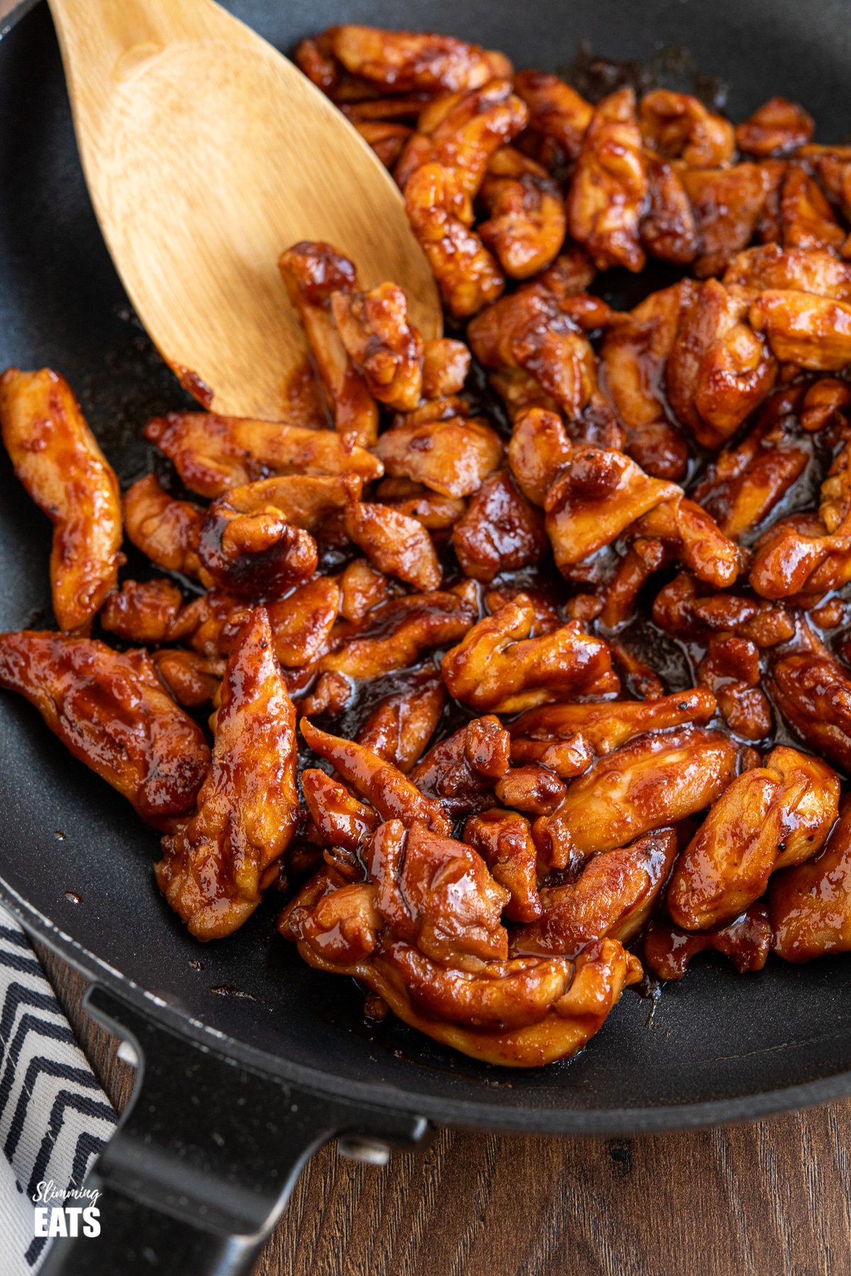 close up of sweet and sticky chicken in black frying pan