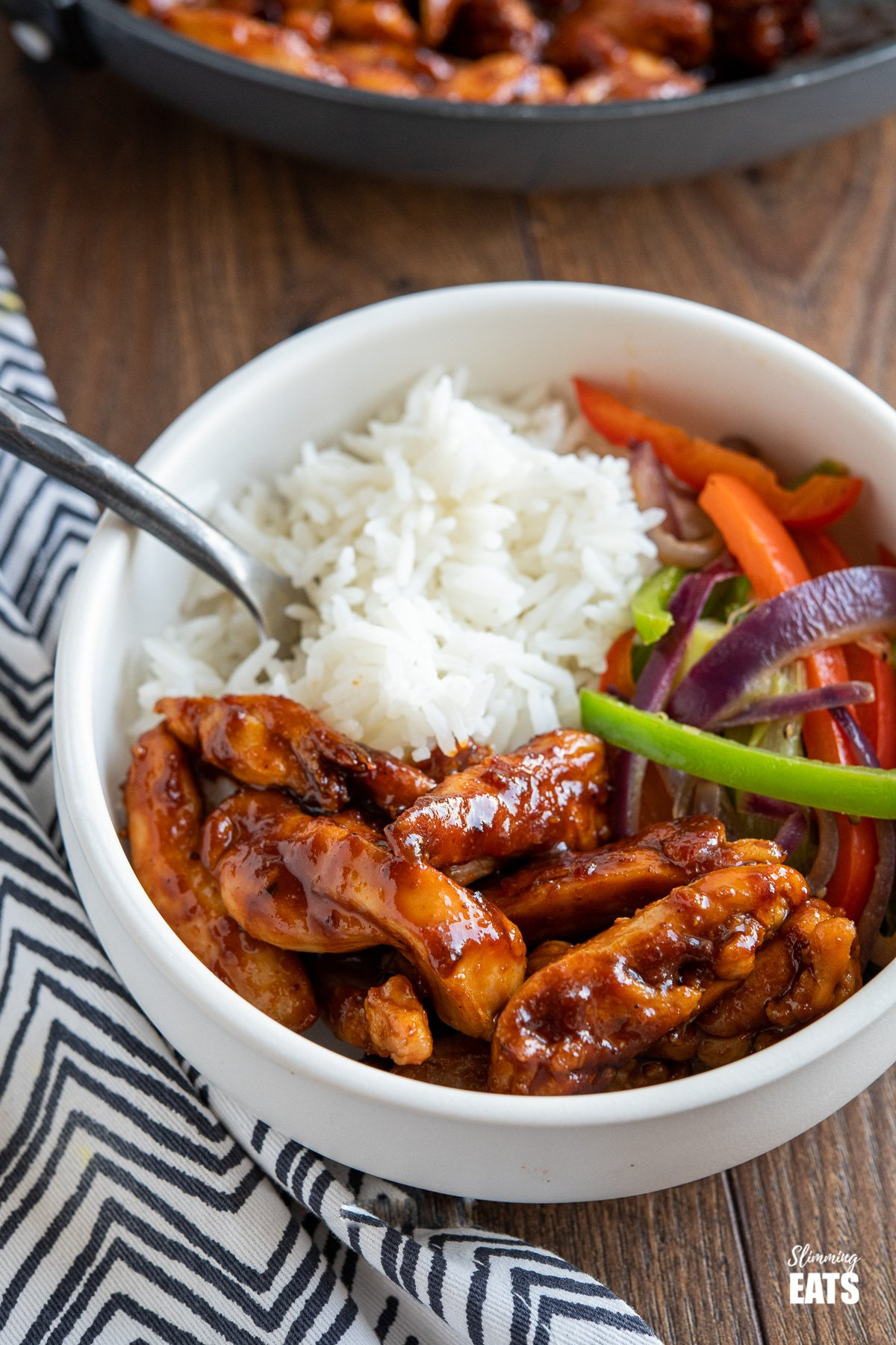 sweet and sticky chicken in white bowl with rice and vegetables