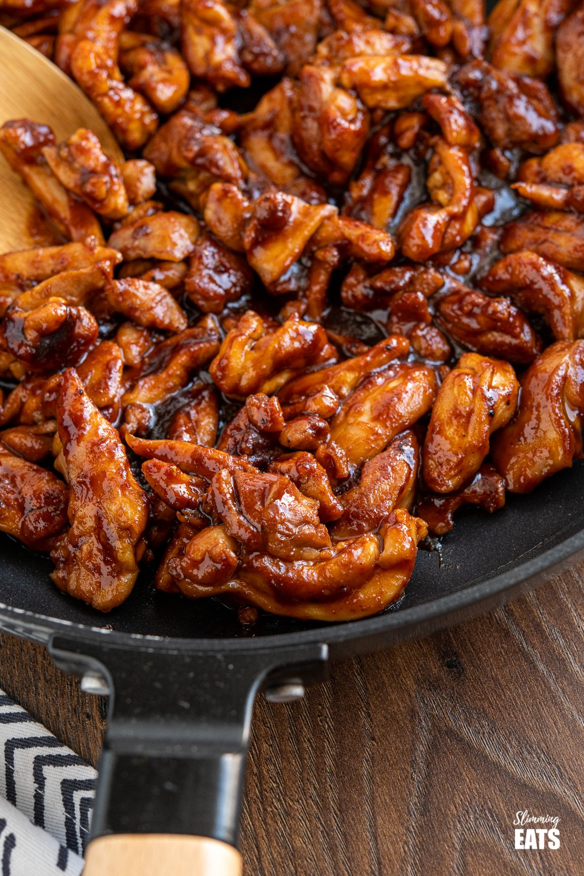 close up of sweet and sticky chicken in frying pan with wooden handle