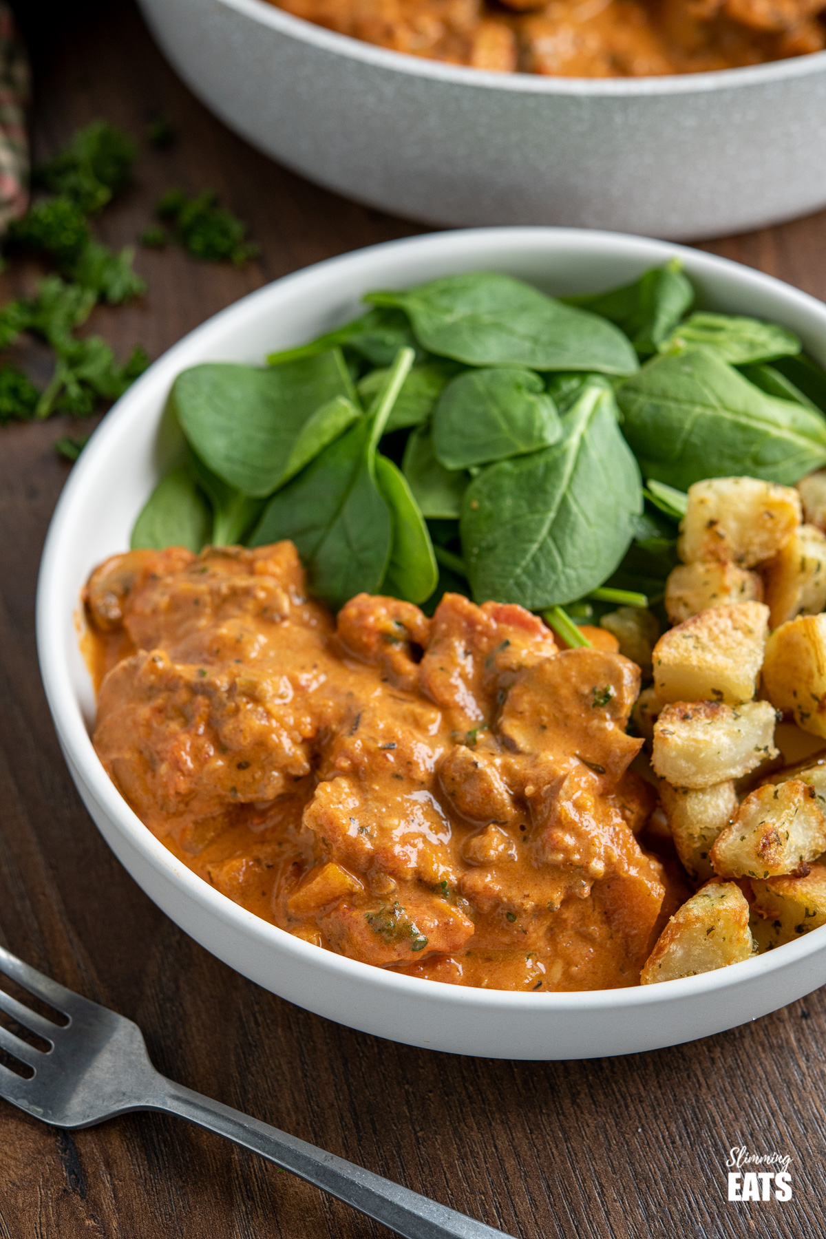 creamy pork casserole in white bowl with garlic and herb potatoes and spinach
