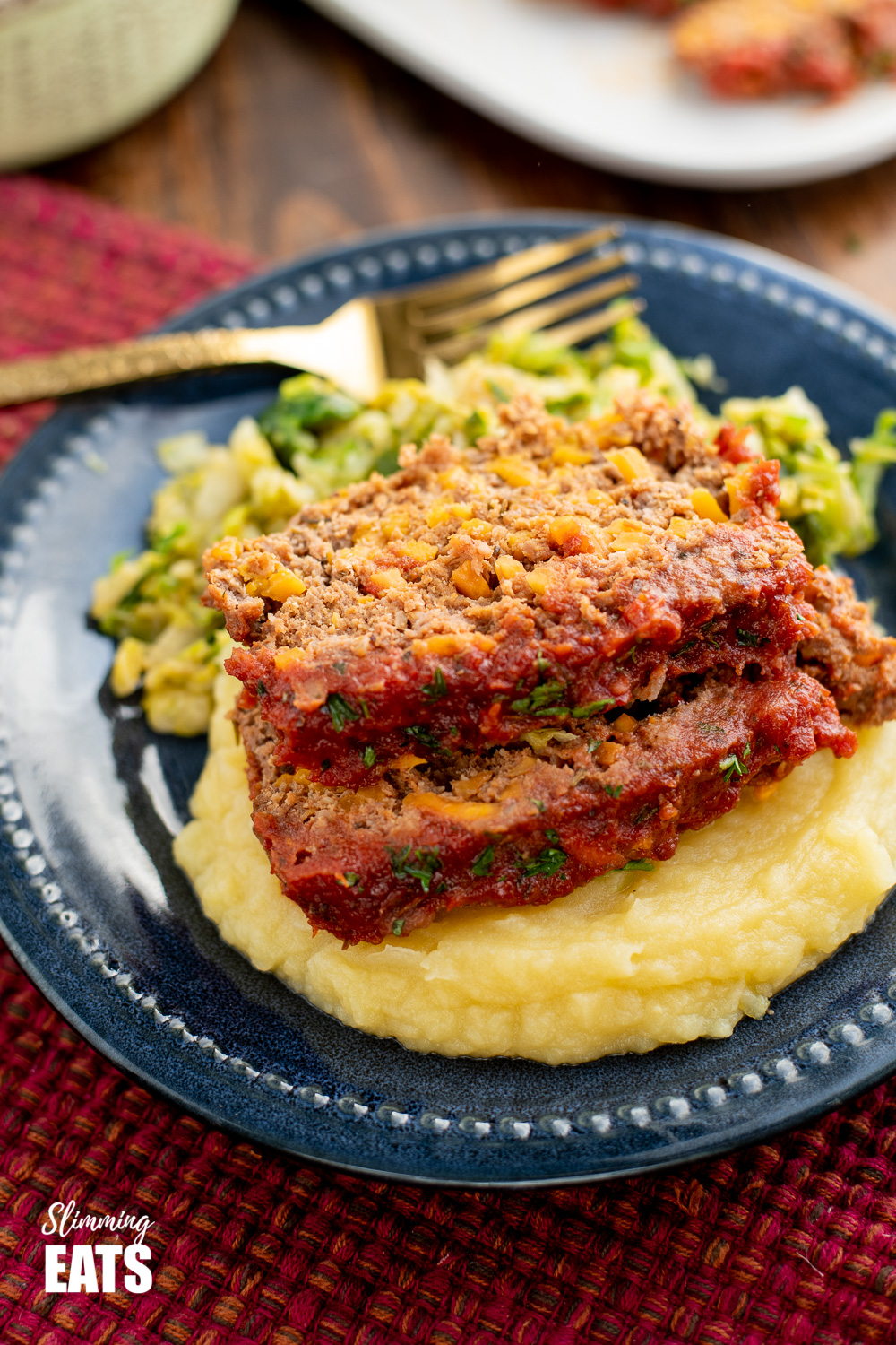 beef and sweet potato meatloaf over mashed potatoes on a navy blue plate.