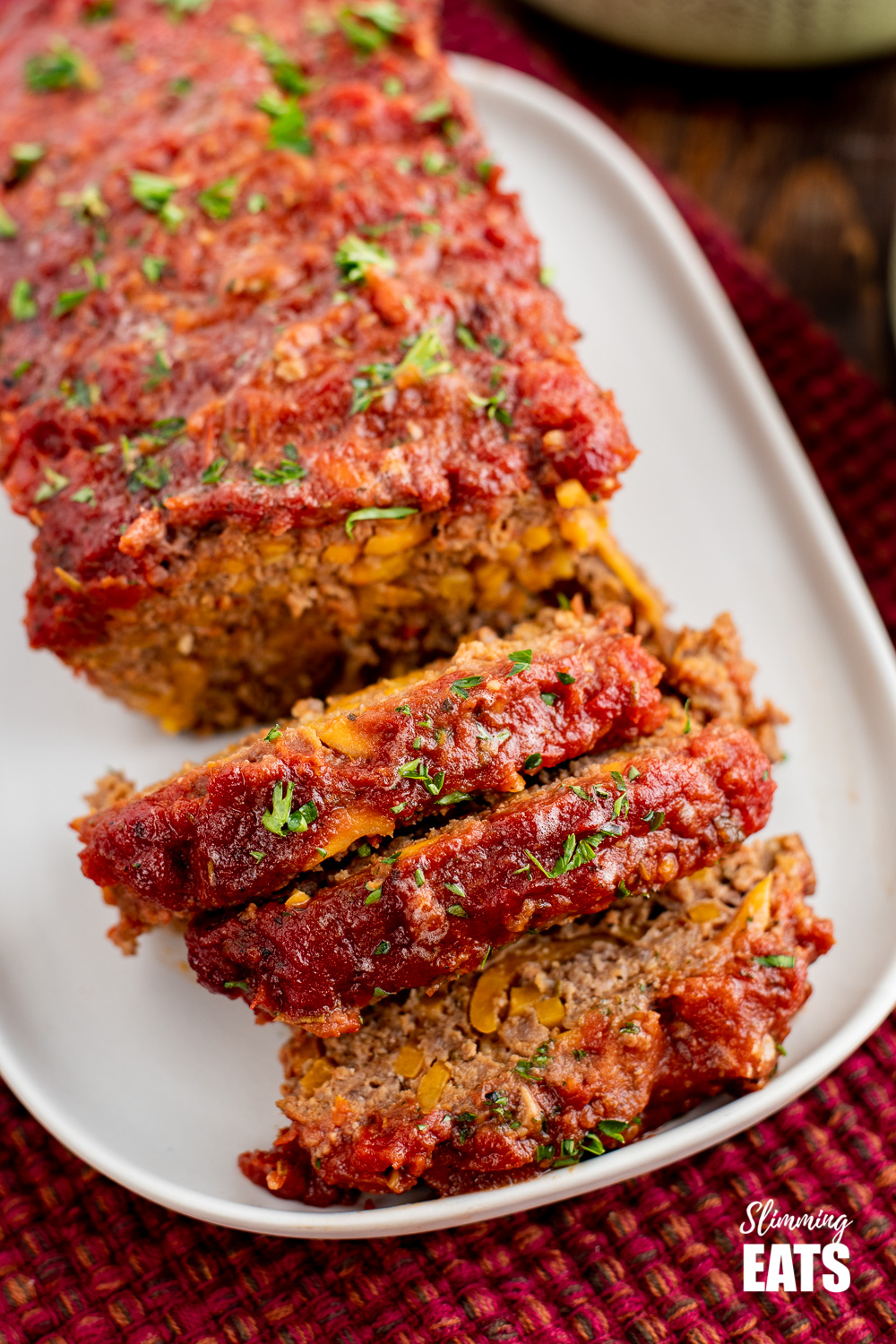 close up of sliced beef and sweet potato meatloaf on a white plate
