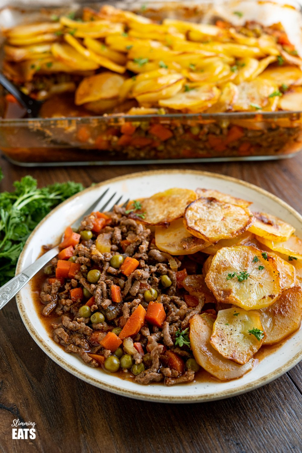 serving of crispy potato topped pie minced beef hotpot on plate with oven proof dish behind