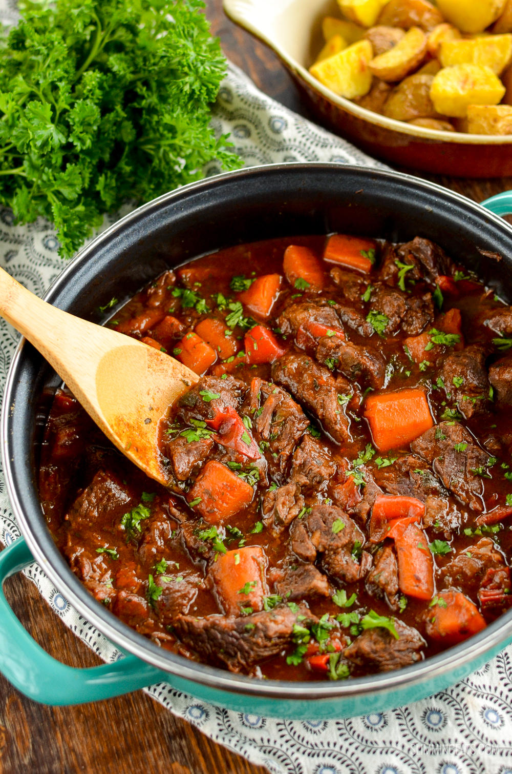 balsamic braised beef in a casserole pan with wooden spoon