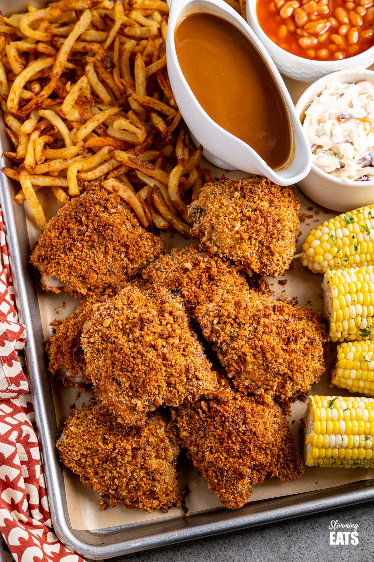 close up of oven baked kfc style chicken feast on a parchment lined baking tray