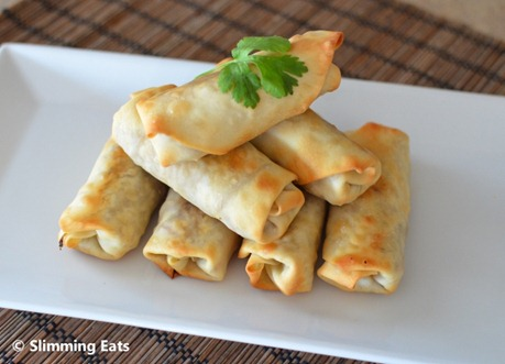 Chicken and vegetable baked spring rolls on white plate