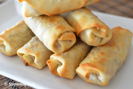 close up of chicken and vegetable baked spring rolls on white plate