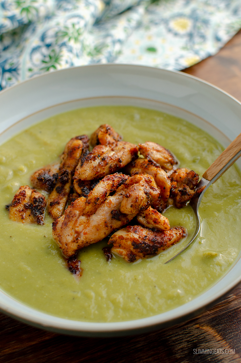 seasoned chicken topped asparagus soup in green bowl with spoon