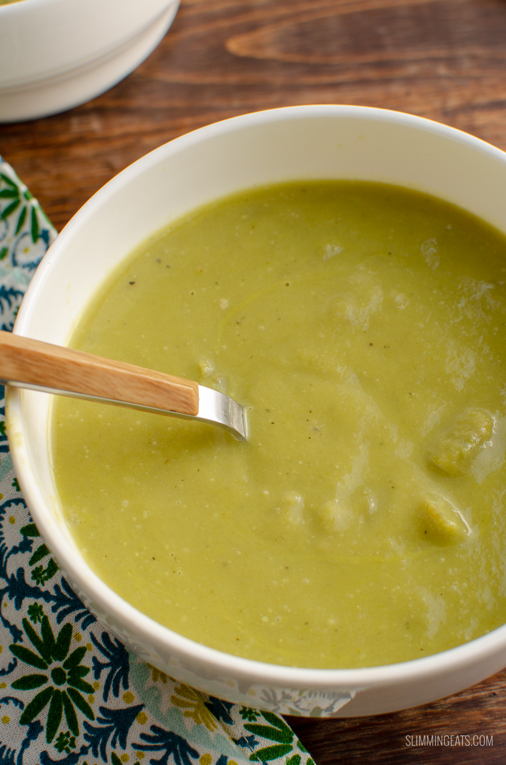 close up of asparagus soup in white bowl