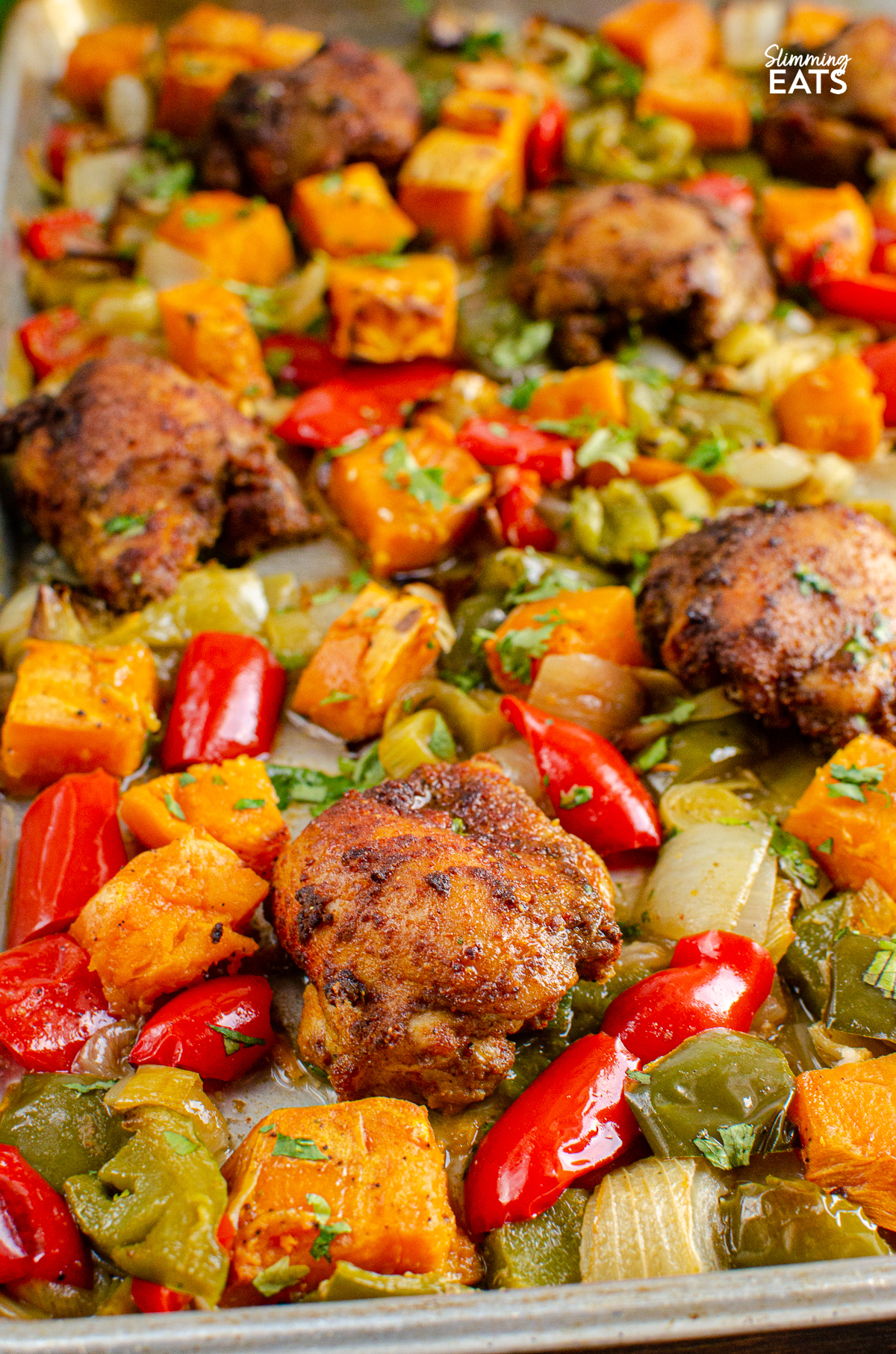 close up of Seasoned Chicken and Roasted Sweet Potato and vegetables baked on a  Tray