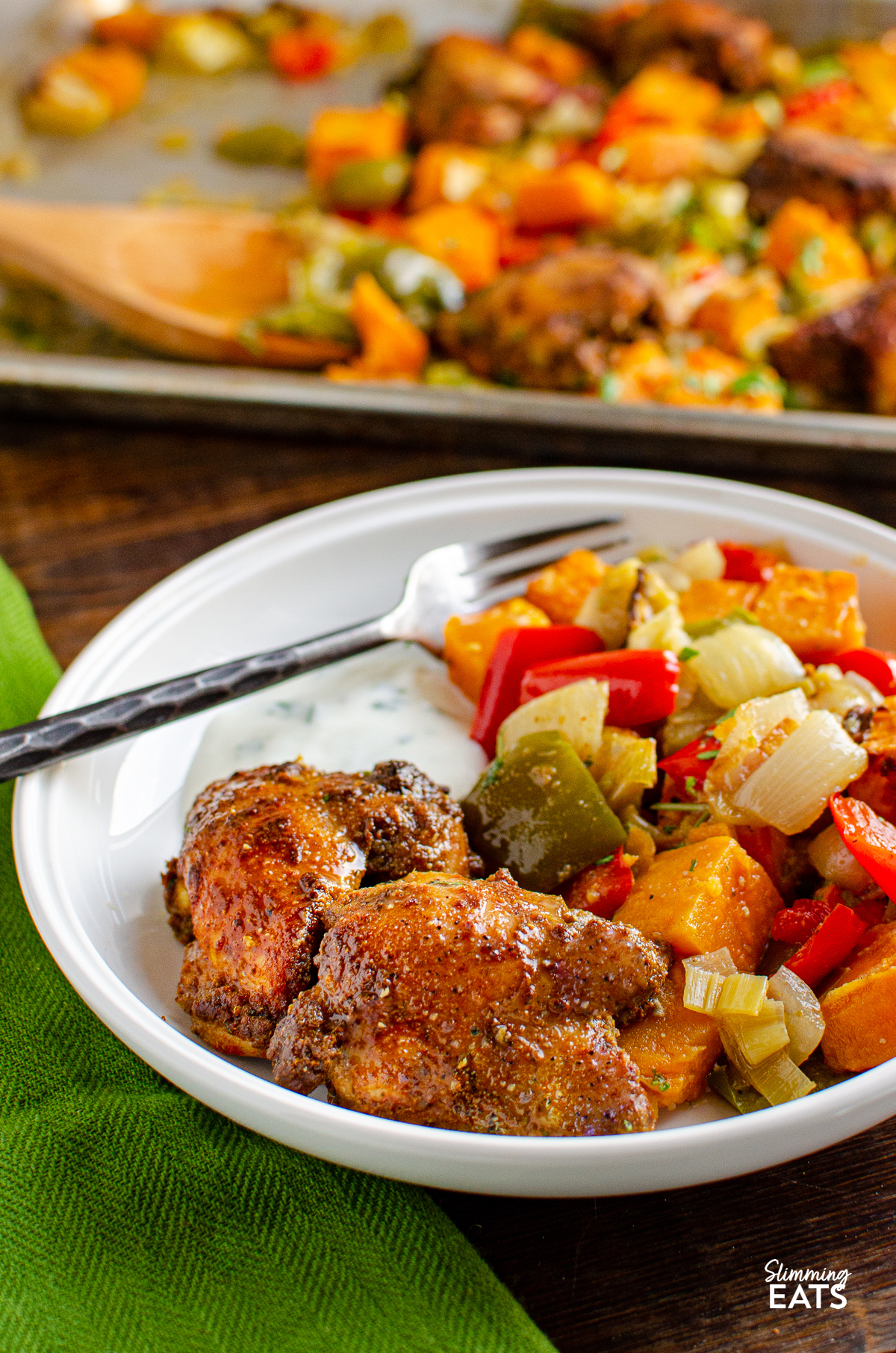 Seasoned Chicken and Roasted Sweet Potato and vegetables baked on a  Tray in a white bowl with served with some yoghurt with lemon juice and cilantro.