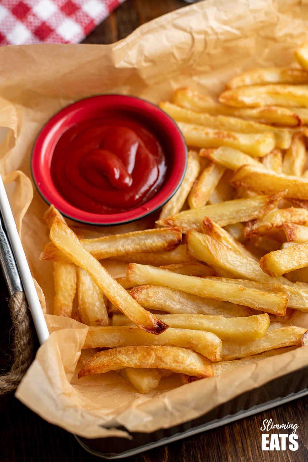 perfect baked oven fries on parchment lined white tray with dish of ketchup