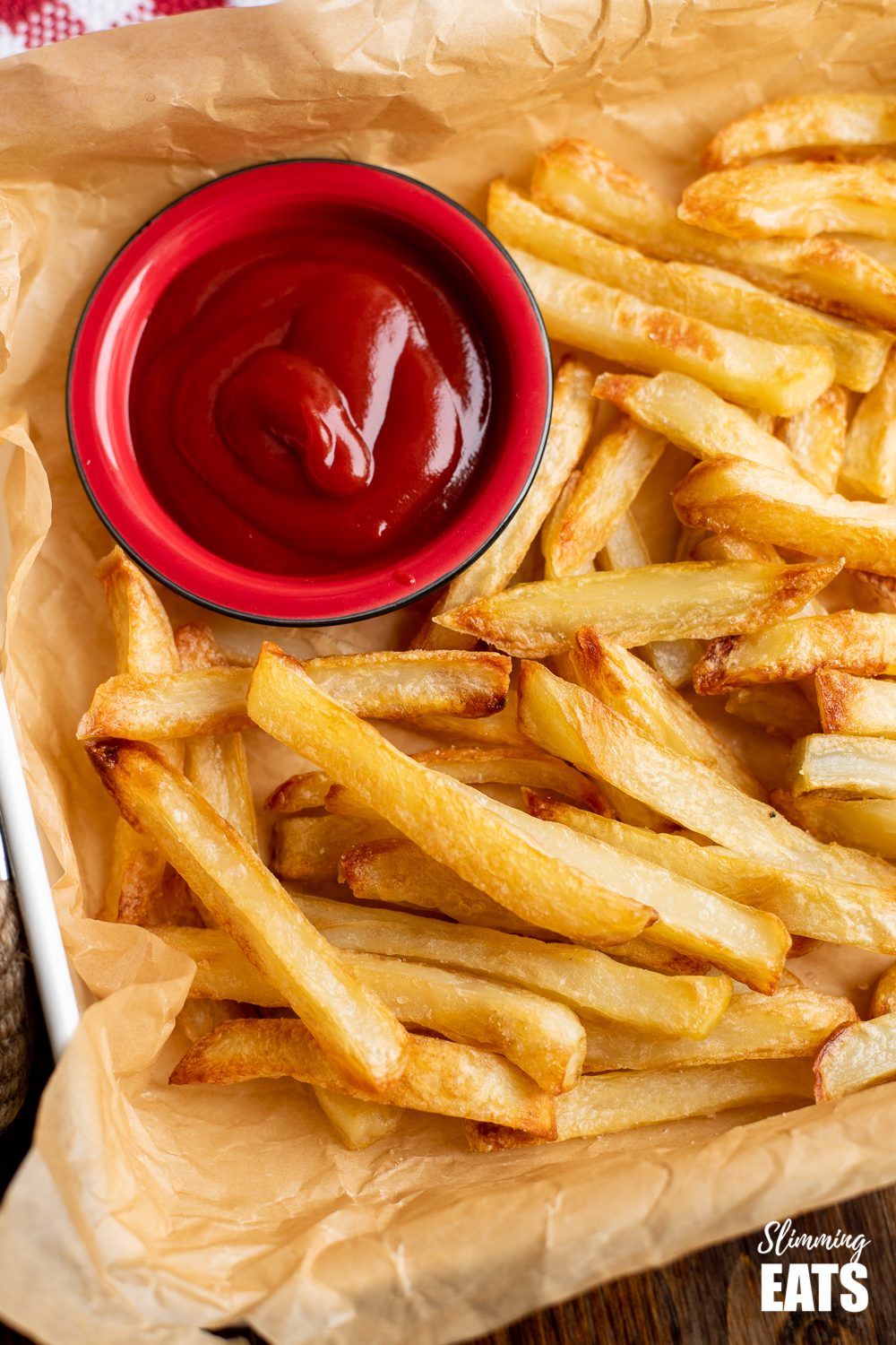 perfect baked oven fries on parchment with dish of ketchup