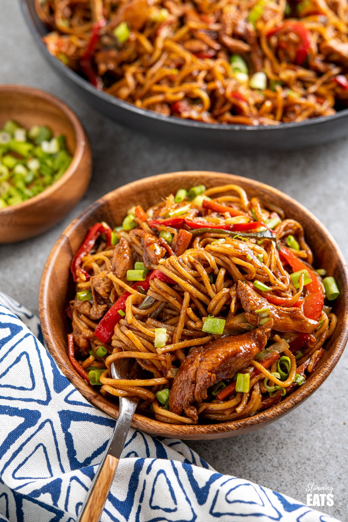 serving of hoisin chicken noodles in wooden bowl with fork place to left in bowl and frying pan of noodles in background