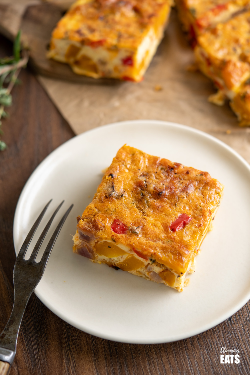 slice of roasted butternut squash and red pepper quiche in cream plate with rustic fork