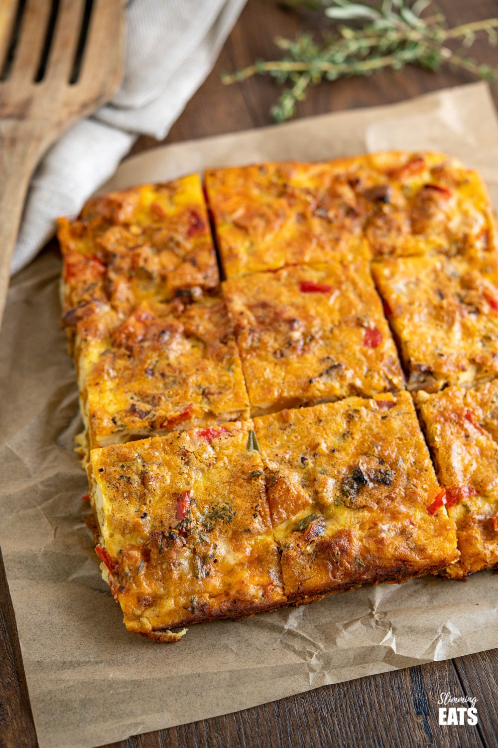 sliced roasted butternut squash and red pepper quiche on parchment paper