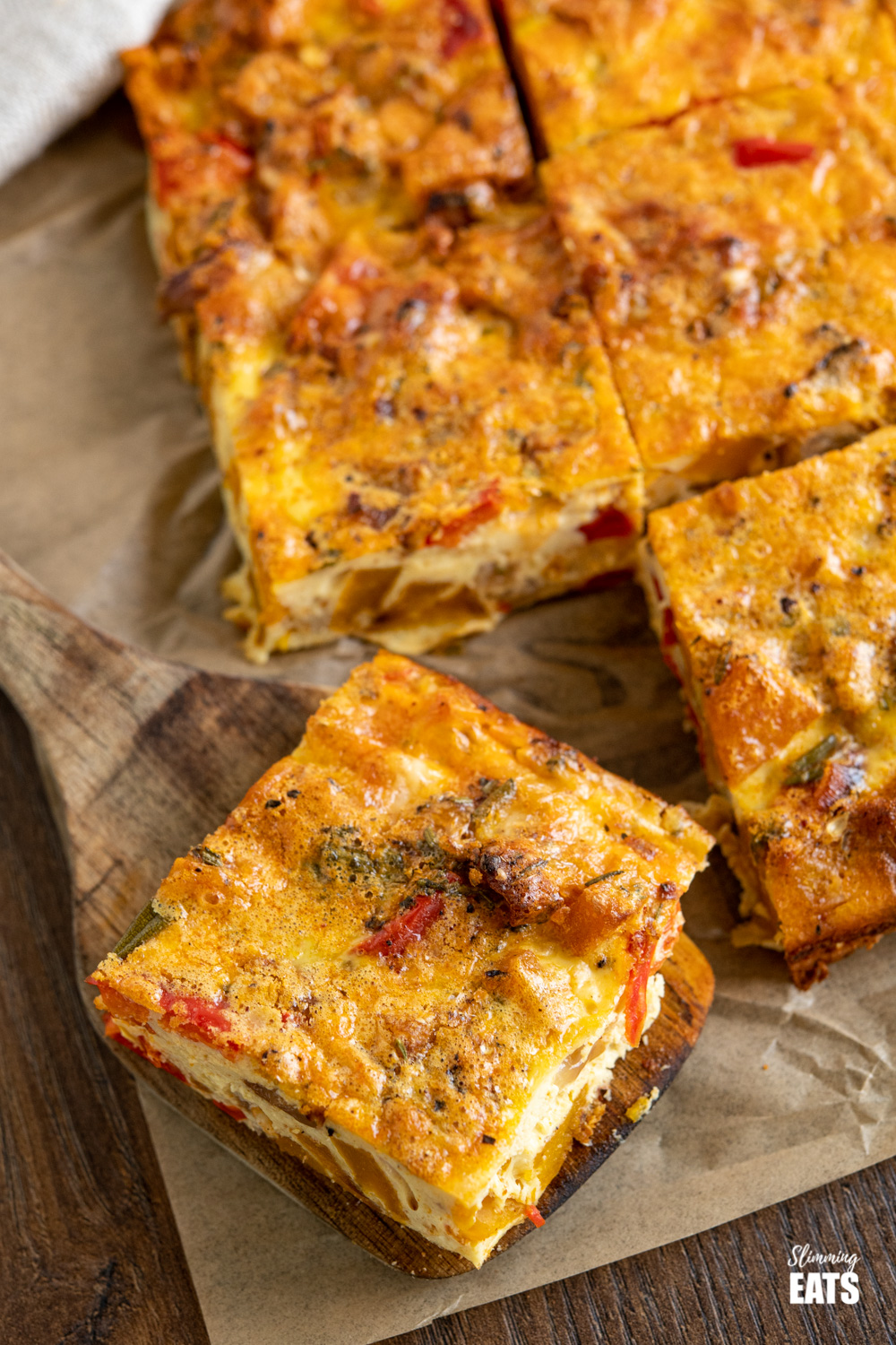 close up of sliced roasted butternut squash and red pepper quiche on parchment paper